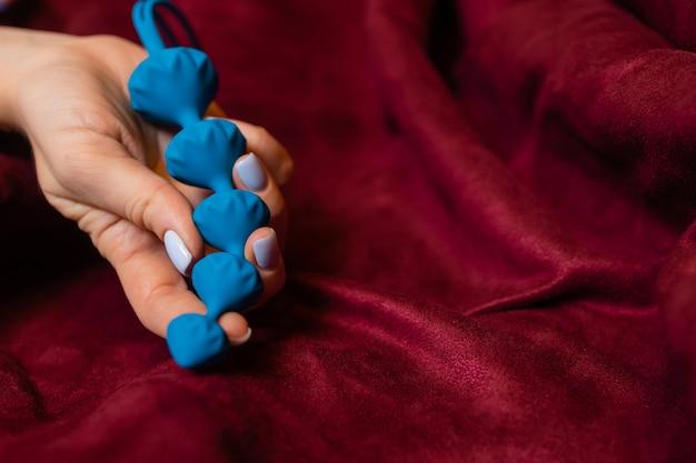 Donna che tiene le palle anali nel letto primo piano