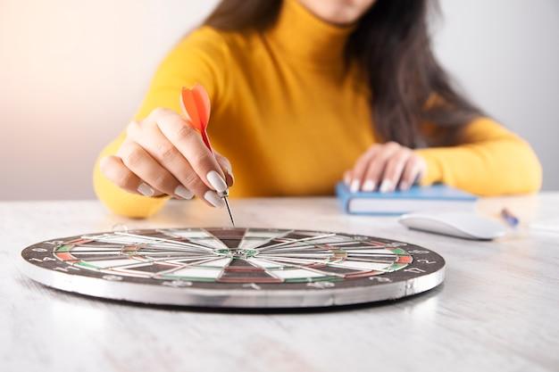 Donna che mantiene la freccia nel bersaglio sul tavolo