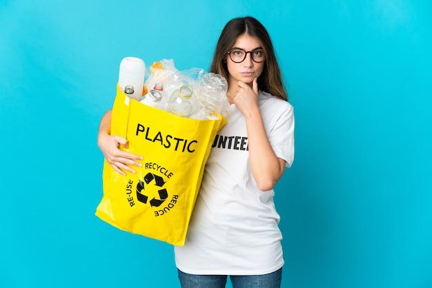 Donna che tiene una borsa piena di bottiglie da riciclare sul pensiero blu