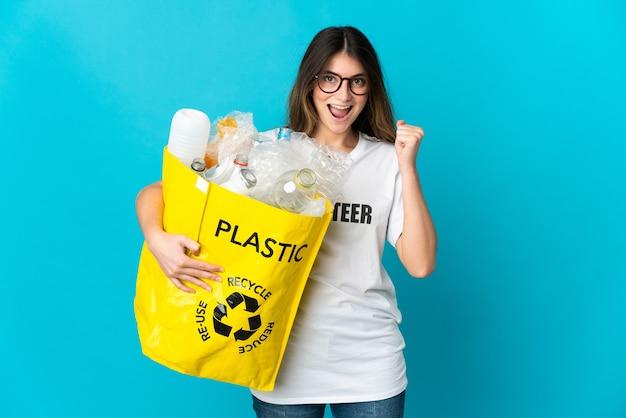 Donna che tiene una borsa piena di bottiglie da riciclare isolata sull'azzurro che celebra una vittoria nella posizione del vincitore