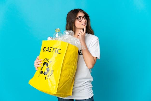 Donna che tiene una borsa piena di bottiglie da riciclare isolato sull'azzurro che ha dubbi mentre osserva in su