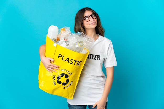 Donna che tiene una borsa piena di bottiglie da riciclare isolata sull'azzurro e alzando lo sguardo