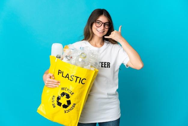 Donna che tiene una borsa piena di bottiglie da riciclare isolato su blu che fa il gesto del telefono. richiamami segno