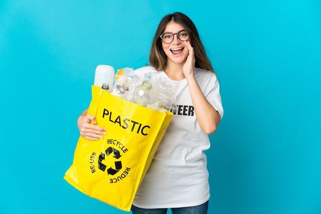 Donna che tiene una borsa piena di bottiglie da riciclare isolato su blu che grida con la bocca spalancata