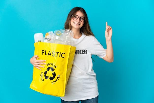 Donna che tiene una borsa piena di bottiglie da riciclare isolata sulla rappresentazione blu e alzando un dito in segno del meglio