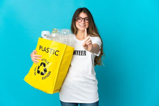 Donna che tiene una borsa piena di bottiglie da riciclare isolato sulla rappresentazione blu e alzando un dito