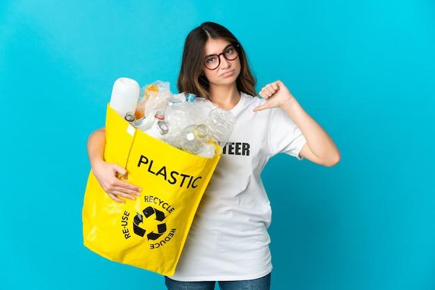 Donna che tiene una borsa piena di bottiglie da riciclare isolato sul blu che mostra il pollice verso il basso con espressione negativa
