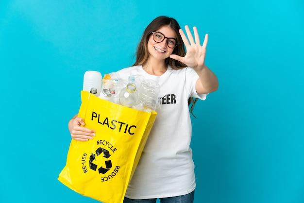 Donna che tiene una borsa piena di bottiglie da riciclare isolato sulla parete blu contando cinque con le dita