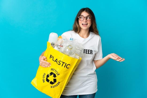 Donna che tiene una borsa piena di bottiglie da riciclare isolato sul blu con espressione di sorpresa mentre guarda di lato