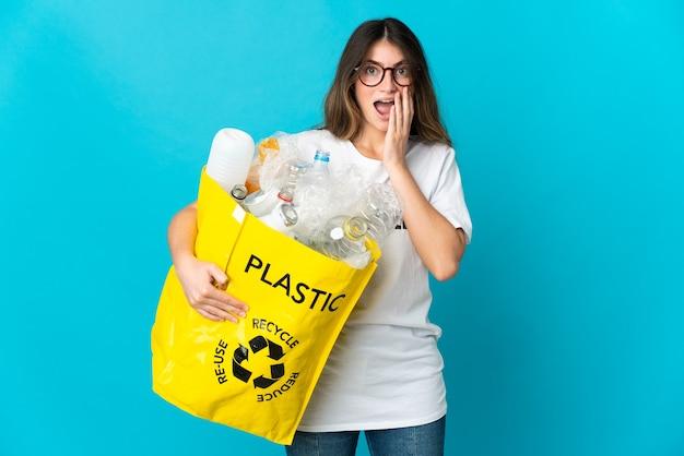 Donna che tiene una borsa piena di bottiglie da riciclare isolato sull'azzurro con espressione facciale sorpresa e scioccata