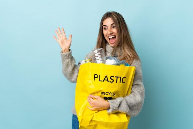 Donna che tiene una borsa piena di bottiglie di plastica