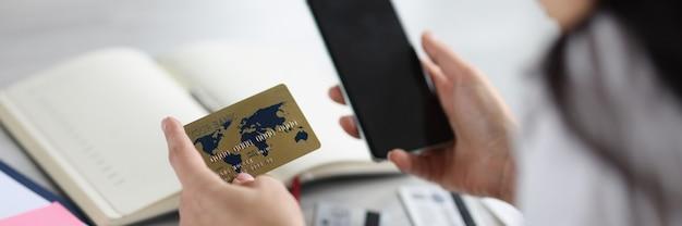 Donna che tiene la carta di credito bancaria e il telefono nelle sue mani il pagamento delle fatture concept