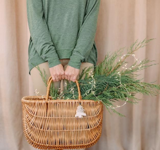 Donna che tiene un cesto con aghi di natale e un cervo giocattolo di legno di simbolo