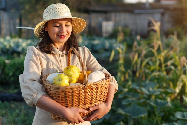 Donna che mantiene un cesto con un raccolto di verdure in mano.