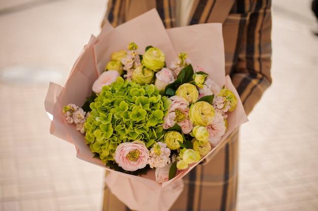 Donna che tiene un bellissimo mazzo di fiori avvolti in carta artigianale il giorno di autunno