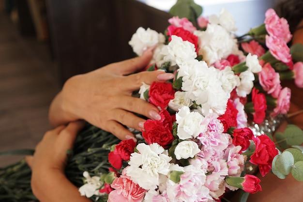 Donna che tiene in mano un bellissimo bouquet di fiori sboccianti colorati di rose fresche quicksand