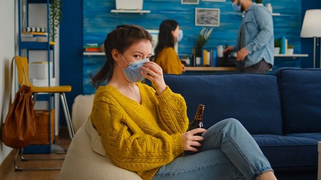 Donna che tiene in mano una bottiglia di birra che beve guardando la telecamera, rilassandosi sul divano, trascorrendo del tempo con gli amici mantenendo le distanze sociali con la maschera facciale in soggiorno prevenendo la diffusione del coronavirus.