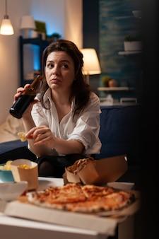 Donna che mantiene una bottiglia di birra rilassante sul divano in soggiorno guardando serie di documentari