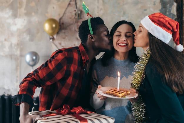 Donna che mantiene la torta di compleanno si prepara a soffiare una candela, amici intorno a baciare le guance.