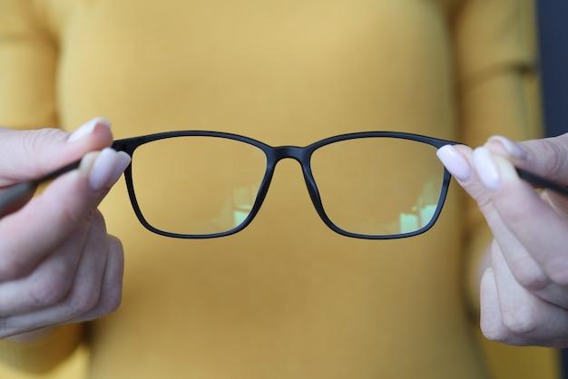 Donna che tiene gli occhiali neri nel suo primo piano di braccia