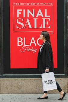 Donna che tiene una borsa della spesa del venerdì nero
