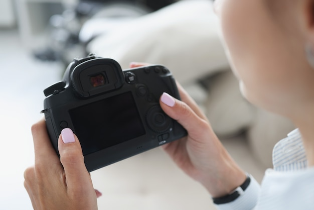 Donna che tiene la macchina fotografica professionale nera in primo piano delle mani
