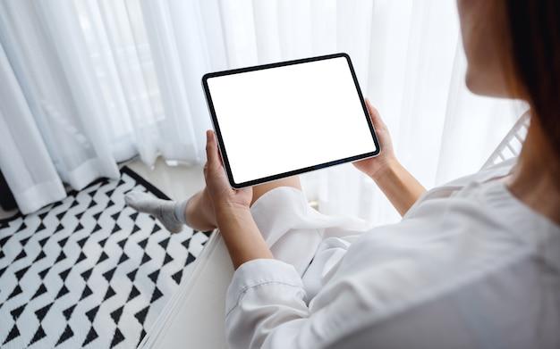Di una donna in possesso di tablet pc nero con schermo desktop bianco bianco mentre era seduto in camera da letto con sentirsi rilassato al mattino