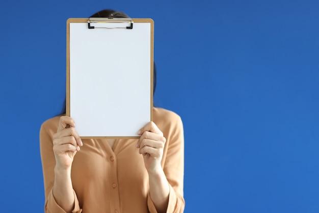 Donna che tiene un documento vuoto negli appunti nelle sue mani davanti al viso