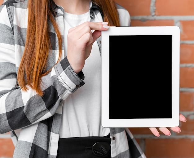 Donna che tiene il dispositivo in bianco del ipad