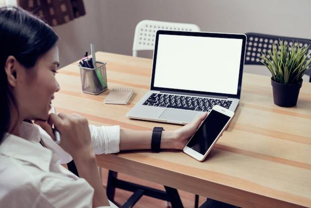 Donna in possesso di un telefono schermo vuoto e un computer portatile e mettere un orologio intelligente, effetto pellicola.
