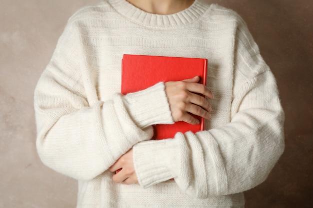 Libro della tenuta della donna contro spazio marrone, vista frontale