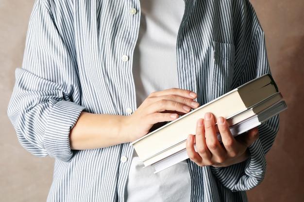 Libri della tenuta della donna contro fondo marrone, fine su