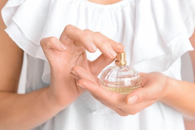 Donna che mantiene una bottiglia di profumo, primo piano