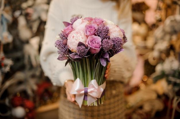 Donna che mantiene un bouquet di teneri fiori di colore rosa e viola con steli verdi