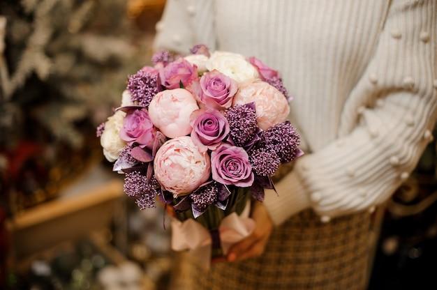 Donna che mantiene un bouquet di teneri fiori di colore rosa e viola