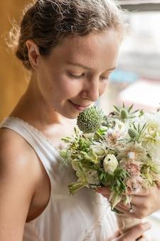 Donna con in mano un mazzo di fiori bianchi