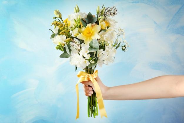 Donna che mantiene il bouquet con i fiori di fresia sulla luce