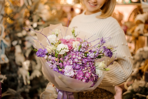 Donna che tiene un bouquet con fiori rosa, viola e bianchi avvolti in carta trasparente opaca