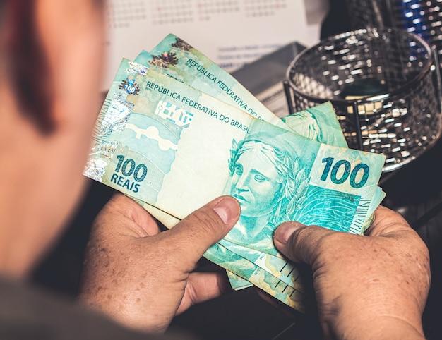 Una donna con in mano banconote vere brasiliane