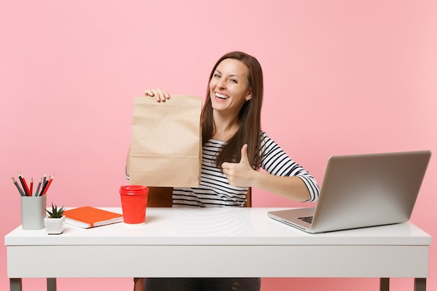 Donna che tiene il sacchetto di carta marrone chiaro vuoto vuoto che mostra il pollice sul lavoro in ufficio con il computer portatile isolato su sfondo rosa. servizio di corriere per la consegna di prodotti alimentari dal negozio o dal ristorante all'ufficio.