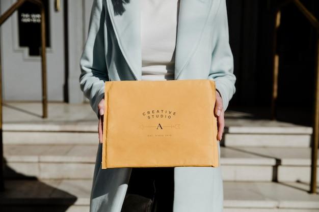 Donna che tiene un modello di busta marrone davanti a un edificio