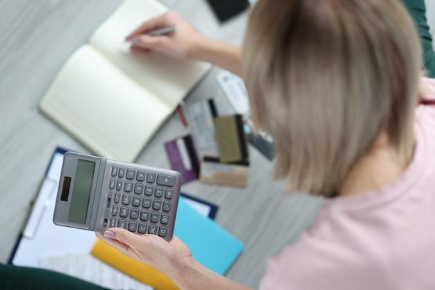 Calcolatrice della holding della donna nelle mani e scrittura nel primo piano del taccuino. concetto di contabilità domestica