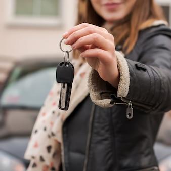 Donna che tiene le chiavi della macchina davanti a una macchina