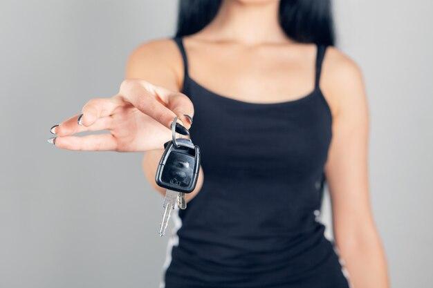 Donna che tiene le chiavi della macchina su sfondo grigio