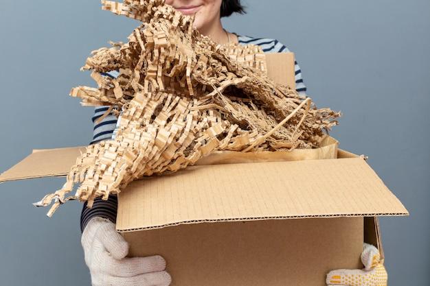 Donna che mantiene la scatola di cartone con carta, rifiuti di cartone, spazzatura per il riciclaggio
