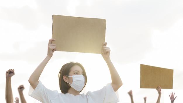 Donna che tiene un cartello del cartone ad una protesta