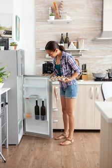 Donna che tiene un cartone animato con uova che guarda nel frigorifero al mattino in cucina
