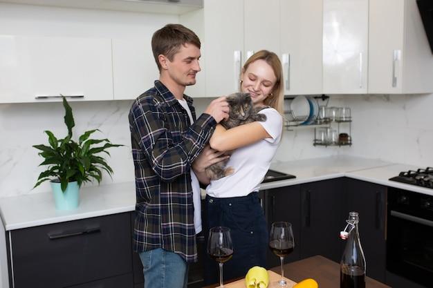 Donna che tiene gatto durante la cottura uomo che abbraccia la moglie