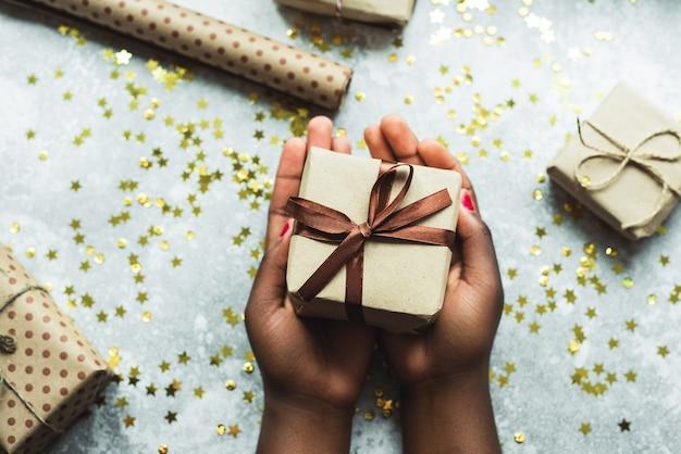 Donna che mantiene il regalo di natale nelle sue mani