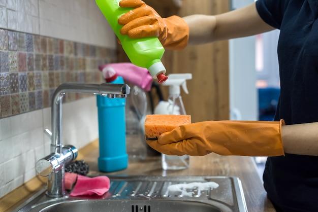 Donna che tiene prodotti e prodotti per la pulizia e pronta per la pulizia. lavori di casa